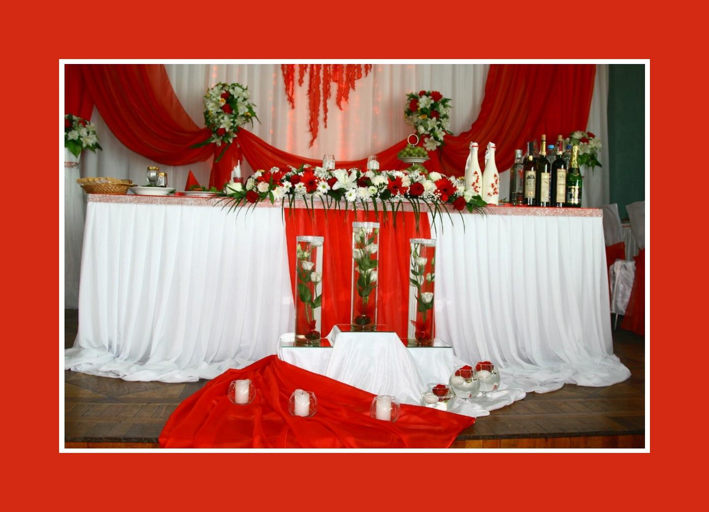 Brautpaartisch mit Rosen und roten Stoffen
