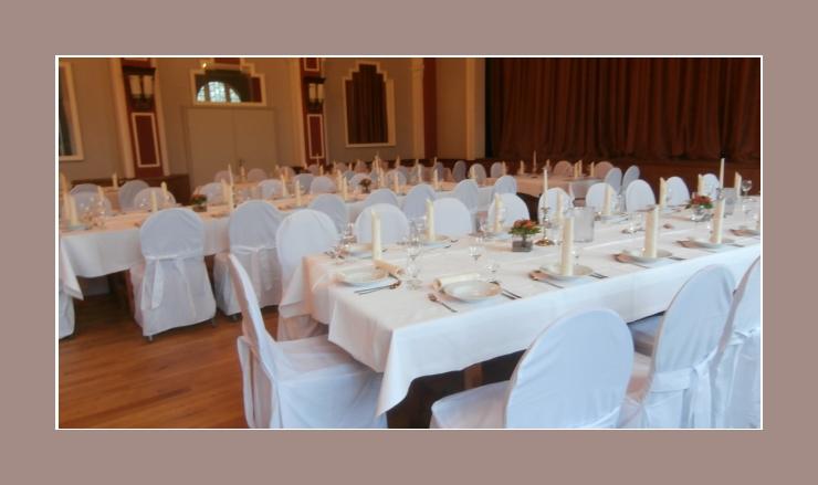 Weiße Hochzeitsdeko mit Kerzen in silbernen Kerzenständern und roten Blumengestecken